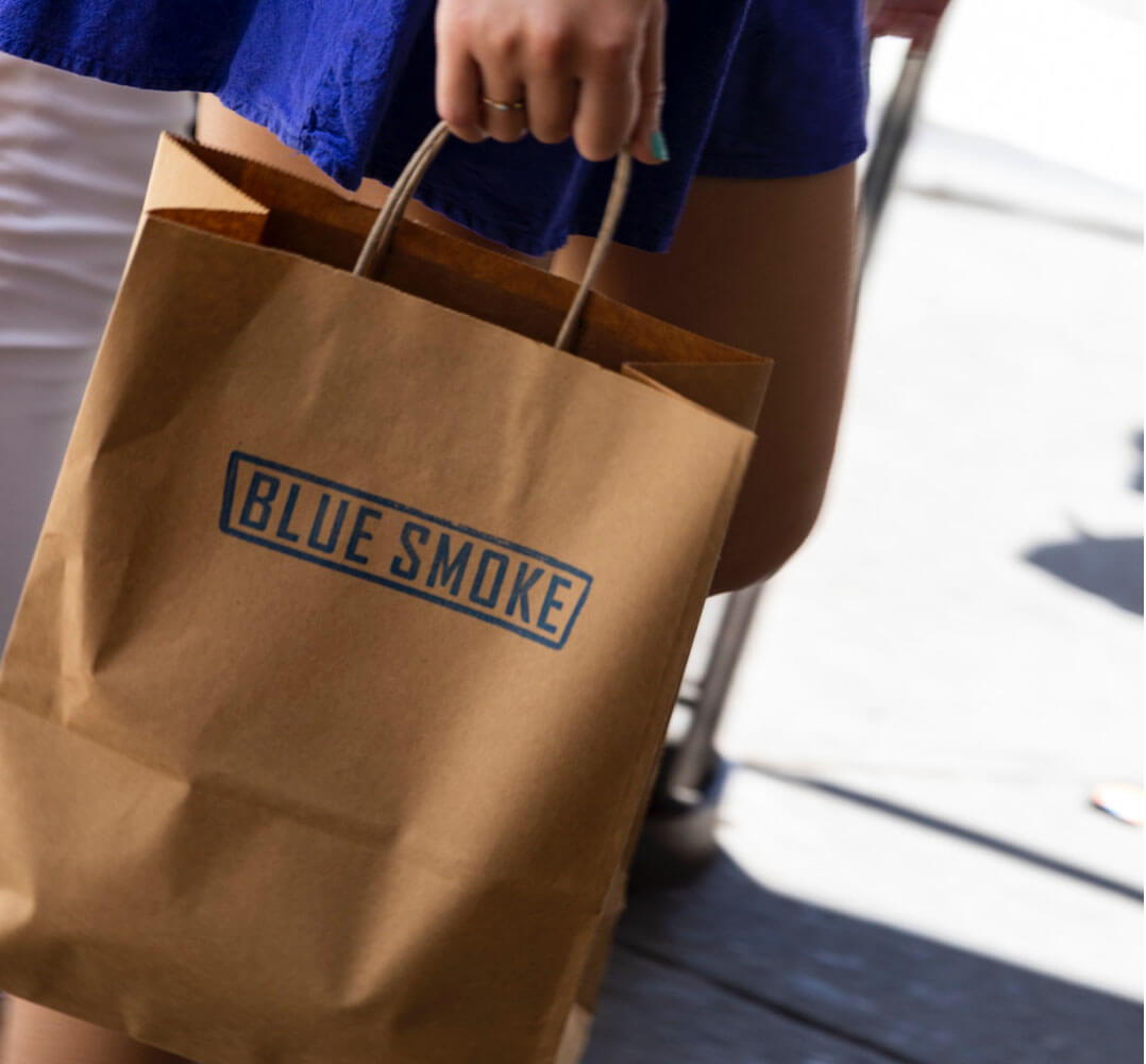 A brown shopping bag with the Blue Smoke logo