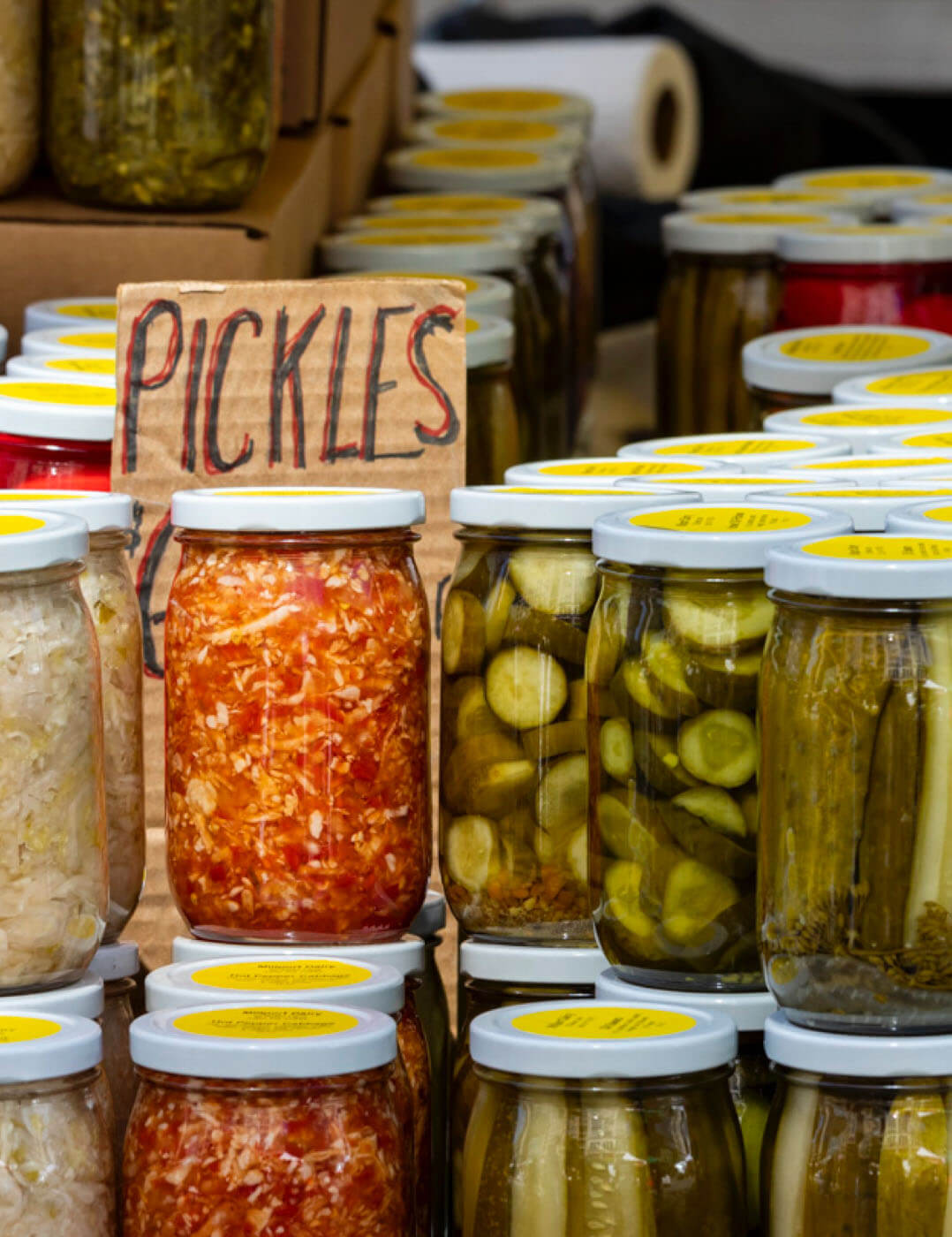 Stacks of jars containing pickles in a shop display